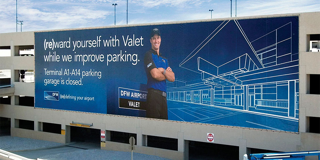 Image of the exterior of a parking garage with a billboard spanning across the side