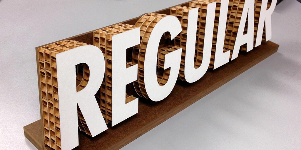 """Image of the word """"Regular"""" cut out of corrugated cardboard"""