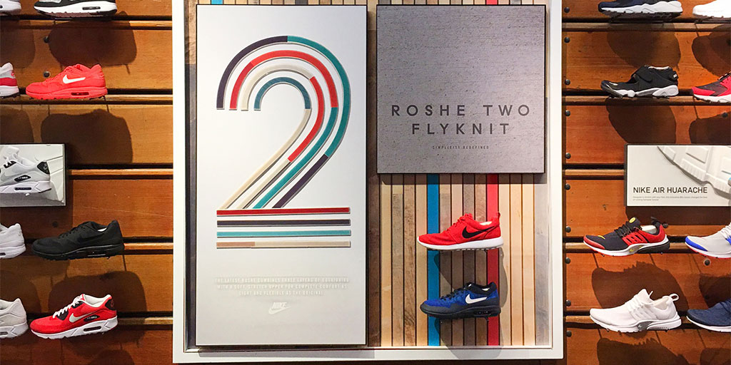 Image of a footwear wall display with custom routed wood 2 standing out from graphic