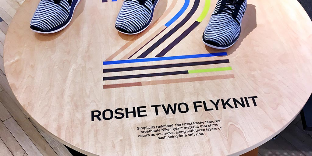 Image of a retail display table with a graphic printed on a wood top