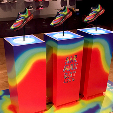 Image of pedestals with rainbow colors printed on them, displaying shoes with matching color pattern