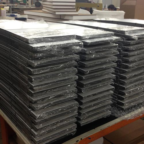 Image of a stack of plex signs waiting to be packed for shipping