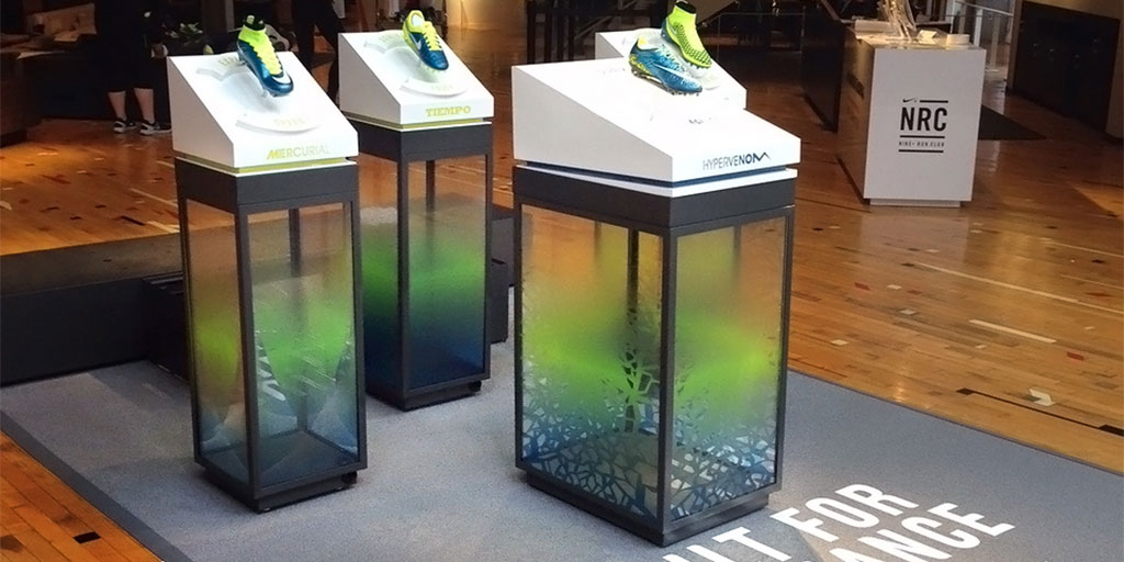 Image of three pedestals with clear acrylic sides printed with a colorful graphic
