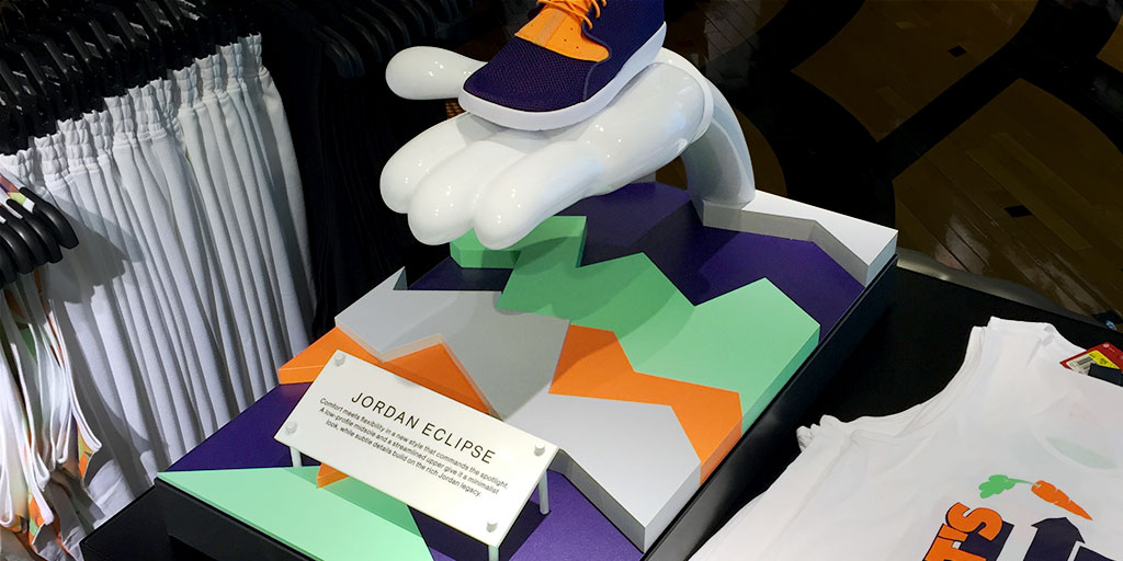 Image of a shoe displayed on a 3d cartoon-esque hand and a colorful cut-out base, with colors that match the colors of the shoe