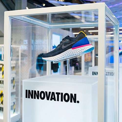 Image of a shoe displayed in a custom pedestal as part of a graphic roll out