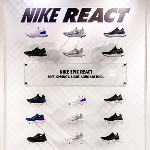 Image of a shoe display wall with custom acrylic sign as part of a national graphic roll out